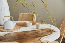 Interior design of stylish dining room interior with family wooden and epoxy table, rattan chairs, flowers in vase and teapot with cups.  Details. Template.