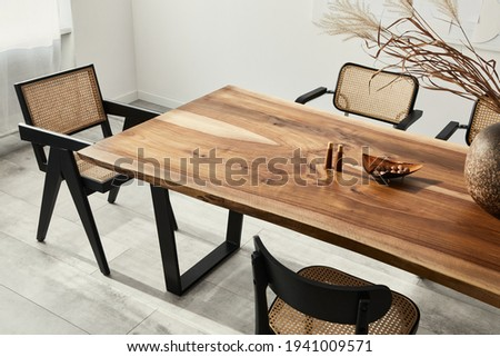 Interior design of stylish dining room interior with family wooden table, modern chairs, plate with nuts,  salt and pepper shakers. Concrete floor. White wall. Template.