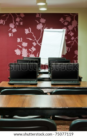 interior design of training class with laptops and flip chart