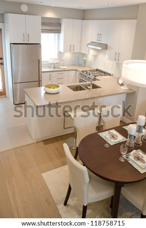 Interior design. Outlook on to the modern dining room with the kitchen as a background