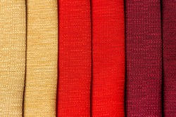 Interior design sample swaps of textured curtain fabric of different shades of gold yellow, red and Bordeaux purple colors for decoration and