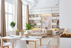 interior design spacious bright studio apartment in Scandinavian style and warm pastel white and beige colors. trendy furniture in the living area and modern details in the kitchen area.