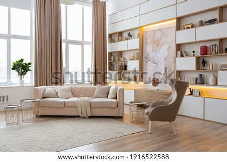 interior design spacious bright studio apartment in Scandinavian style and warm pastel white and beige colors. trendy furniture in the living area and modern details in the kitchen area. Foto stock ©