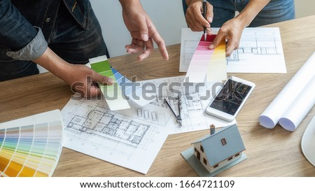 Interior designer and Architect choosing color in color swatch samples chart for house coloring selection in office with blueprint. Construction concept. Foto d'archivio ©