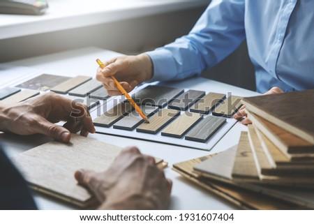 interior designer and customer choosing furniture and flooring materials from samples at design shop Сток-фото ©