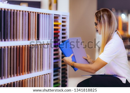 Interior designer, decorator, choosing cabinet panel and countertop material in showroom