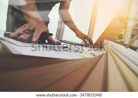 Interior designer hand working with new modern computer laptop and pro digital tablet with sample material board on wooden desk as concept