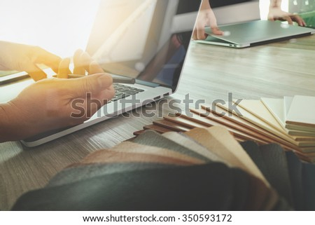 Interior designer hand working with new modern computer laptop and pro digital tablet with sample material board and digital design diagram layer on wooden desk as concept