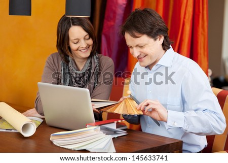 Interior designer in a client meeting sitting at a desk with an attractive woman showing her various samples