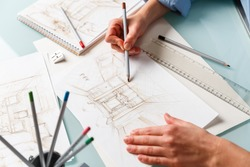 Interior designer making hand drawing pencil sketch of a bathroom. Interior design projects concept