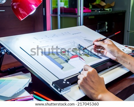 Interior designer's hand working with illustration sketch at modern home office