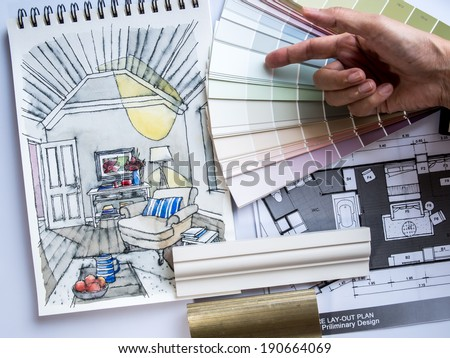 Interior designer's hand working with illustration sketch material and color samples