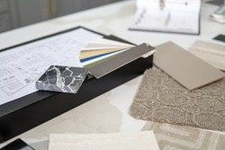 Interior designer's working table, an architectural plan of the house, a color palette, furniture and fabric samples. Drawings and plans for house decoration.
