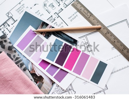 Interior designer\'s working table, an architectural plan of the house, a color palette, furniture and fabric samples in grey and pink color. Drawings and plans for house decoration.