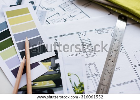 Interior designer\'s working table, an architectural plan of the house, a color palette, furniture and fabric samples in yellow and grey color. Drawings and plans for house decoration.