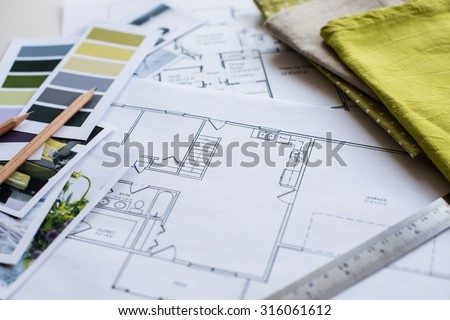 Interior designer's working table, an architectural plan of the house, a color palette, furniture and fabric samples in yellow and grey color. Drawings and plans for house decoration. #316061612