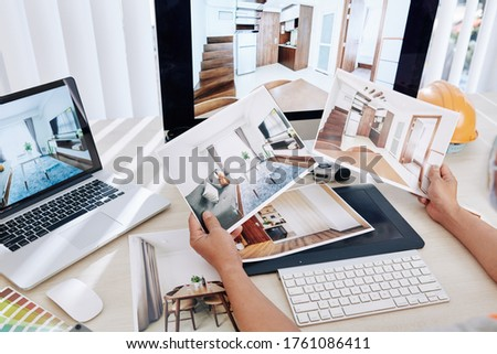 Interior designer sitting at desk and looking at printed photos of clients rooms after renovation Stockfoto ©