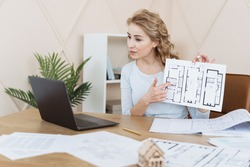 Interior designer talking with client at video call, showing architecture blueprint, pointing on sketch of new apartment. Woman sitting in office, looking at laptop display with online conference