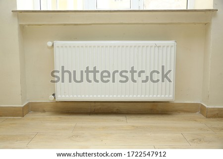 Interior detail. White metal radiator on a white wall. Central heating radiator .just installed a new steel heating radiator. Full view of a white radiator against a cream wall