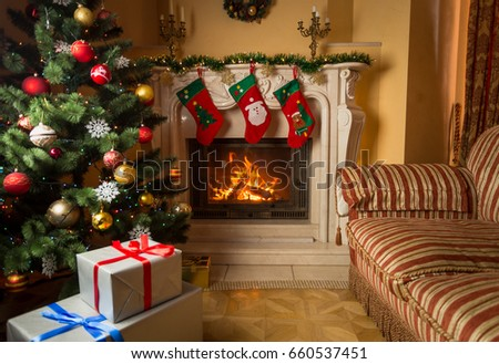 Interior image of living room with burning fireplace, decorated Christmas tree