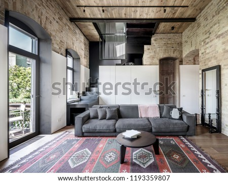 Interior in a loft style with brick walls, wooden ceiling and a parquet with a carpet on the floor. There is a gray sofa with pillows, round table, stair, windows, doors, white lockers, mirror.