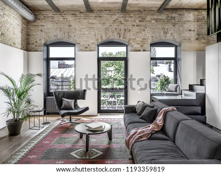Interior in a loft style with brick walls, wooden ceiling and a parquet with carpet on the floor. There is a gray sofa with pillows and plaid, round table, stand, windows, green plant, stair, door.