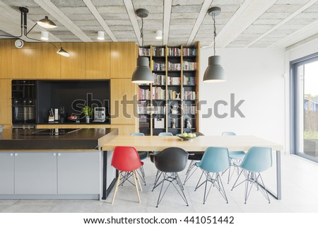 Interior in an industrial style with an open kitchen, dining table and colorful chairs