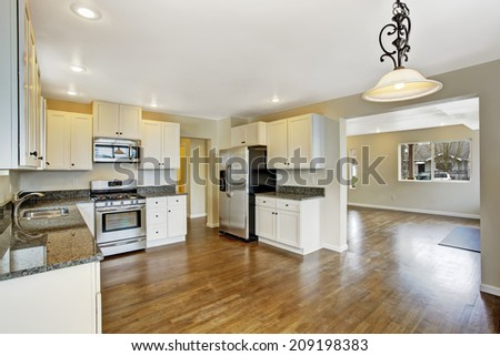 Interior in empty house with open floor plan. Spacious kitchen room with white cabinets and granite tops