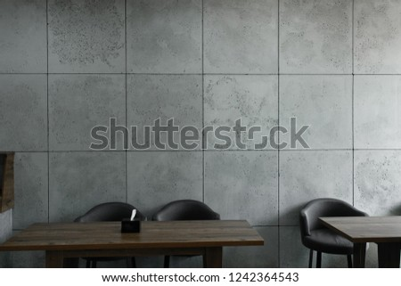 interior in loft style. interior in loft style. table and chairs on a background of a wall of concrete slabs