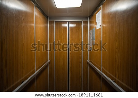 Interior inside a closed clean old Soviet elevator car lined with wood. Foto stock ©