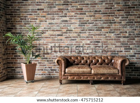 Interior mock up photo. Brownish brick wall with leather sofa and pot with plant. Background photo with copy space for text.