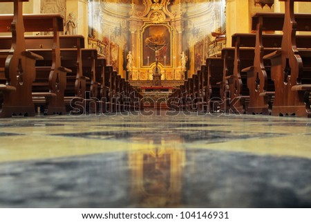 Interior of a beautiful old catholic church from below with marble floor, wooden pews, and light streaming onto altar with Jesus on crucifix