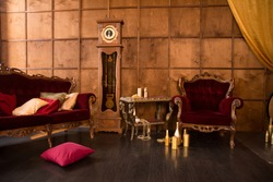 Interior of a beautiful old room with red armchairs against a wooden wall with a high clock