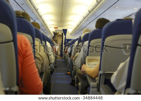 Interior of a commercial airplane. No  recognizable faces - stock photo