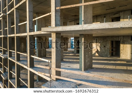 Interior of a concrete residential apartment building room with unfinished bare walls and support pillars for future walls under construction.