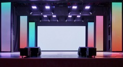 Interior of a conference concert hall or theatre with LED screen on scene and red seats