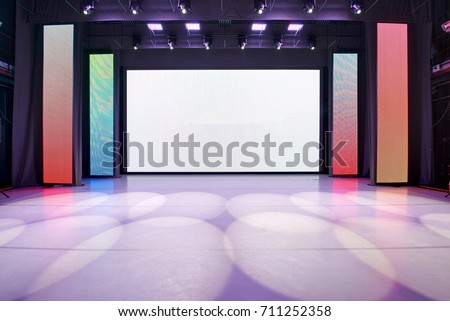 Interior of a conference concert hall or theatre with LED screen on scene and red seats #711252358