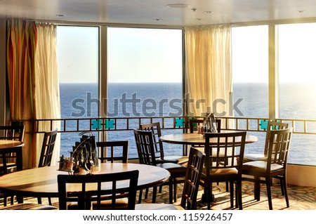interior of a dinner lounge on a cruise ship - with a round table and windows with panorama seaview - stock photo