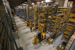 Interior of a distribution warehouse viewed from above. View onto blue storage racks and yellow boxes. Logistics and warehousing in full action with forklift and a lot of goods around