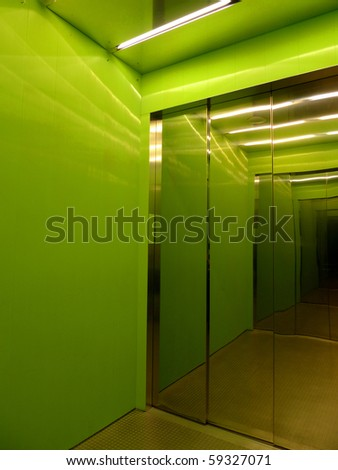 Interior of a green elevator with reflective doors