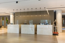 Interior of a hotel lobby with reception desks with transparent covid plexiglass lexan clear sneeze guards