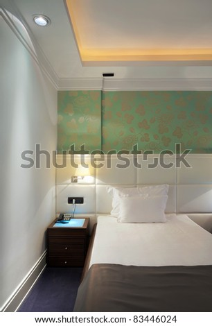 Interior of a hotel room for two, a bed and green wallpapers.