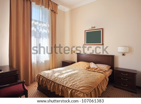 Interior of a hotel room for two, just a bed near window.