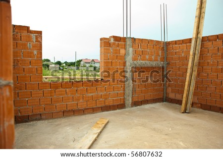 Interior of a house under construction with red brick walls