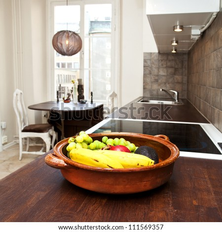 interior of a kitchen with a bowl of fruit in the foreground