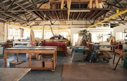Interior of a large carpentry workshop full of workbenches and an assortment of tools, wood and machinery