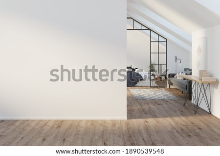Interior of a large light attic with a blank mockup wall, wooden floor. There is a painting with books on a sideboard, a gray modern sofa, a bed with a blanket in the background. Front view. 3d render