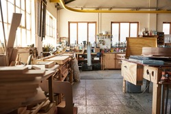 Interior of a large woodworking shop full of tools, machinery and an assortmant of wood planks and boards