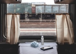 Interior of a long-distance train in Russia. Window in the train compartment. Sanitizer, mask and phone on the table During the coronovirus pandemic COVID 19