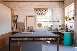 Interior of a manufacturing area of a picture framing studio with a variety of tools and different sized wooden frames